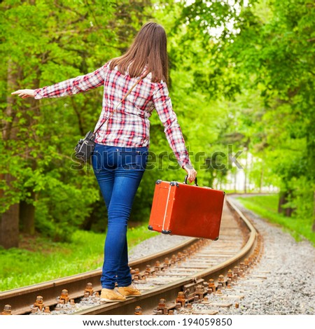 girl with retro brown suitcase walking on the railway - stock photo