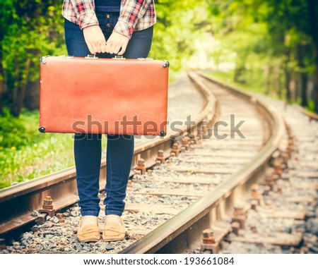 girl with retro vintage suitcase on railway, retro stylized - stock photo