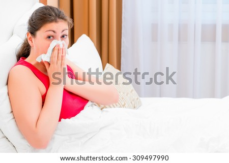 girl with rhinitis blows her nose lying in bed