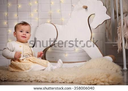 girl with rocking horse in the backdrop of a brick wall with a garland of light bulbs - stock photo
