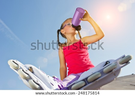 girl with roller skates on her feet sit and drink water, lens flare - stock photo