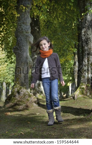 girl with scarf walking on a path in the forest