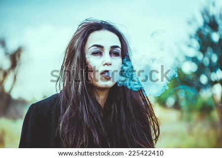 Girl with scary face painting smoking - stock photo