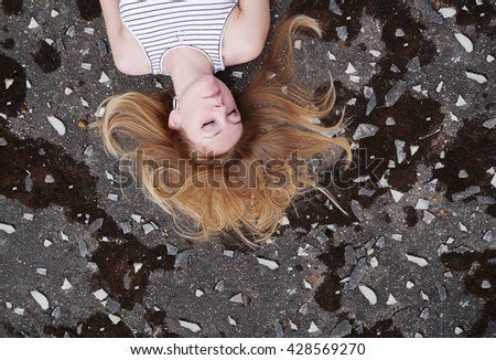 Girl with scattered hair laying on the ground