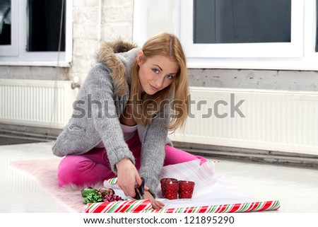 Girl with scissors preparing gifts for party - stock photo