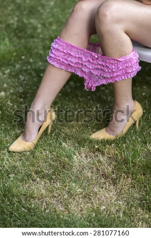 Girl with sexy legs and pink panties pulling down on heels - stock photo