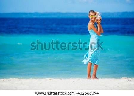 Girl with shell at the beach