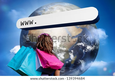 Girl with shopping bags looking at address bar with large earth in blue sky with clouds - stock photo