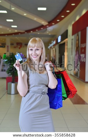 Girl with shopping bags smiling in a store  - stock photo