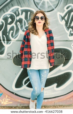 girl with skateboard resting against a wall painted