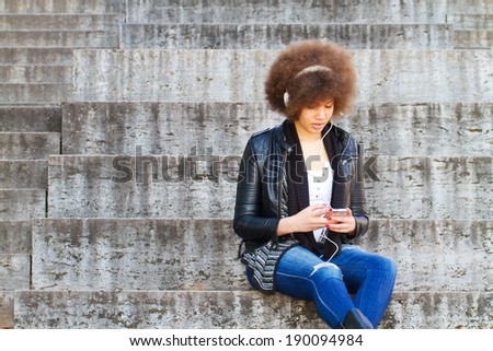 Girl with smart phone sitting on a stairway - stock photo