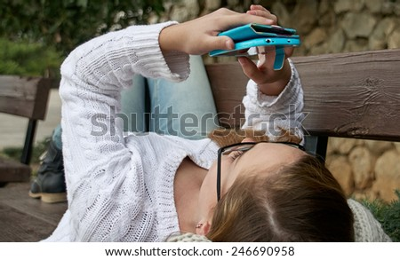 Girl with smartphone is lying on the bench - stock photo