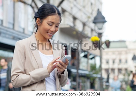 Girl with smartphone walking on city  - stock photo