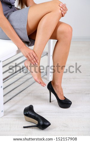 Girl with sore foot isolated on white - stock photo