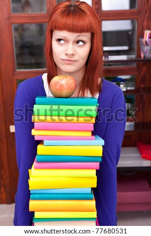 girl with stack color book, thinking about learning
