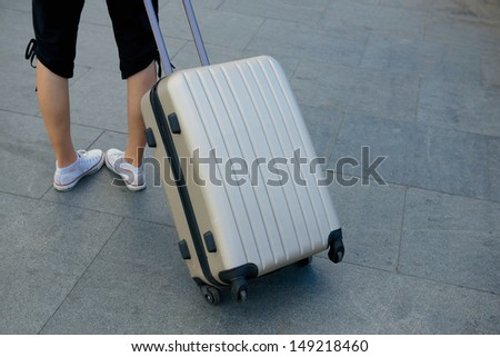 girl with suitcase waiting in terminal - stock photo
