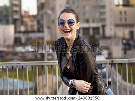 Girl with sunglasses laughing in the city