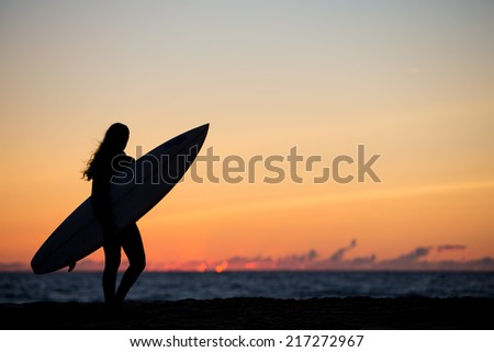 girl with surfboard in sunset