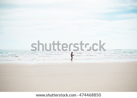 Girl with surfboard is walking along the beach