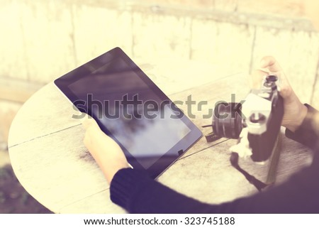 Girl with tablet and old style camera, vintage photo effect - stock photo