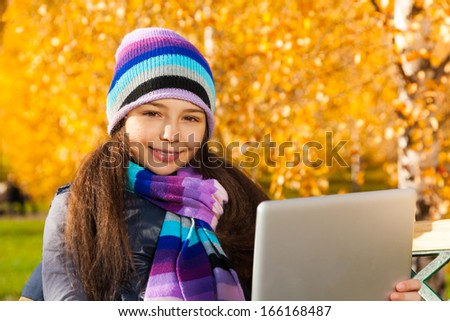Girl with tablet computer 11 years old sitting in the park on sunny autumn day