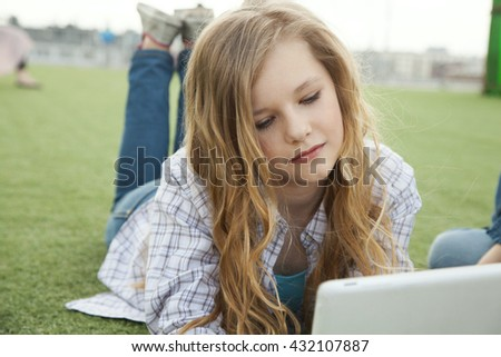 girl with tablet sitting on the roof