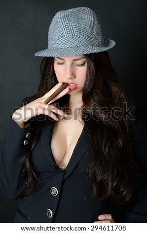 Girl with tail-coat and hat. Female model holding cigar, confident brunette. - stock photo