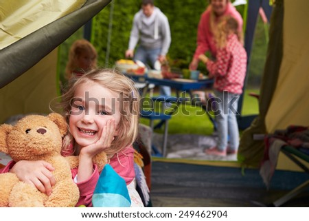 Girl With Teddy Bear Enjoying Camping Holiday On Campsite  - stock photo