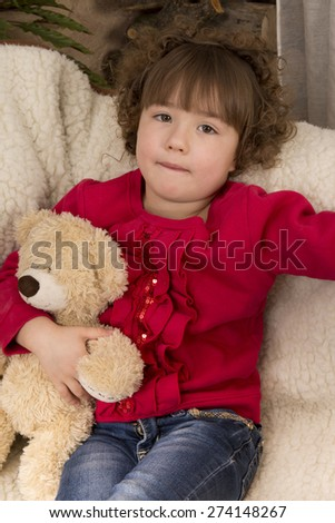 girl with teddy bear in a chair