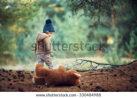 girl with teddy bear walking in the woods