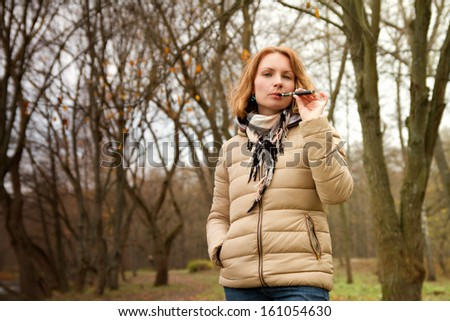 girl with the electronic cigarette in the park autumn - stock photo