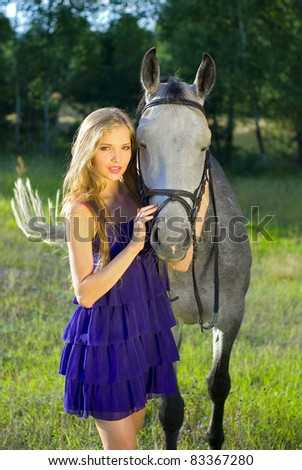 girl with the grey horse on the meadow