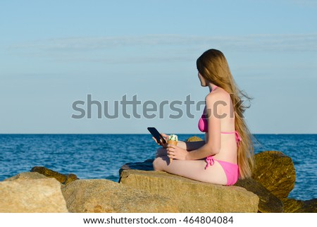 Girl with the phone sitting on the rocks in a bathing suit against the sea, space