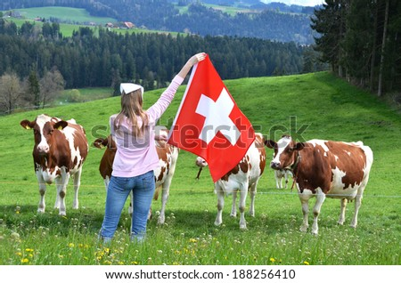 Girl with the Swiss flag against cows. Emmental, Switzerland - stock photo