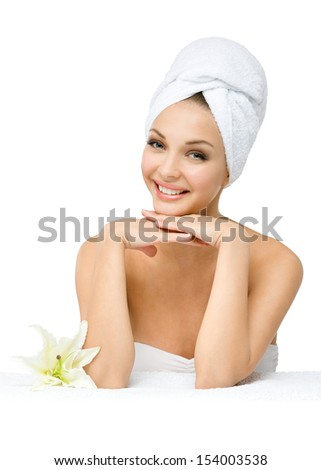 Girl with towel on head touches face sitting near a white lily, isolated on white. Concept of healthcare, beauty and youth
