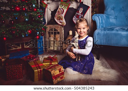 Girl with toy horse in Christmas room