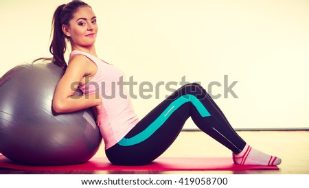 Girl with training equipment. Young female in gym with fit ball. Activity fitness health workout concept. - stock photo