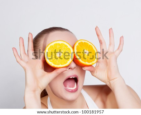 Girl with two halfs of orange in hands