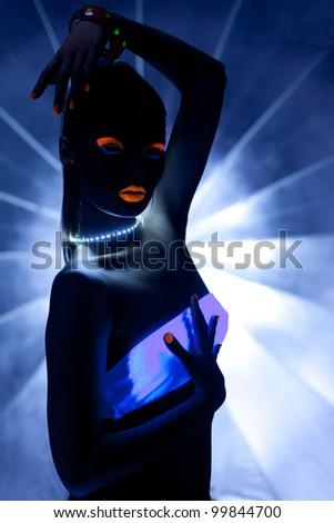 Girl with ultraviolet makeup disco dance in dark - stock photo
