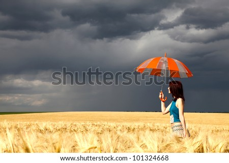 Girl with umbrella at field. Photo with HDR processing.