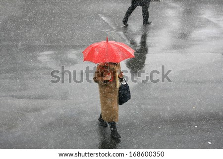 Girl with umbrella during snow storm in the street - stock photo