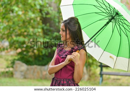 Girl with umbrella in autumn park. Beautiful fashion female portrait in long dress  - stock photo