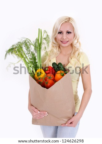 girl with vegetables in shopping bag on white background, healthy eating