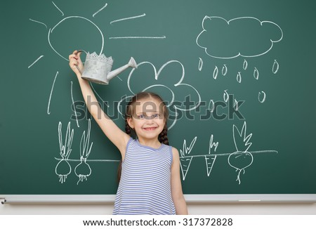 girl with watering can drawing rain on school board - stock photo