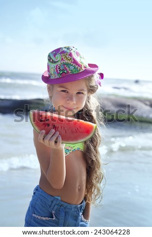 Girl with watermelon on the beach - stock photo
