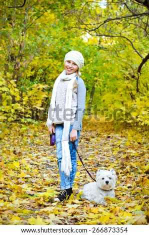 girl with west highland terrier in the park