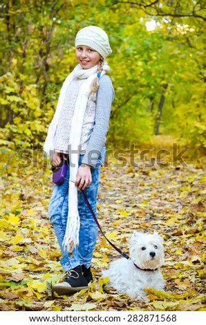 girl with west highland terrier in the park - stock photo