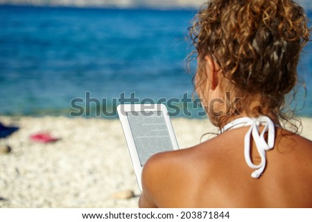 Girl with white hat reads kindle on beach  - stock photo