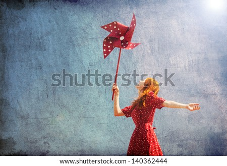Girl with wind turbine at blue sky background.