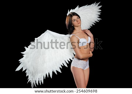 girl with wings in underwear on black background - stock photo